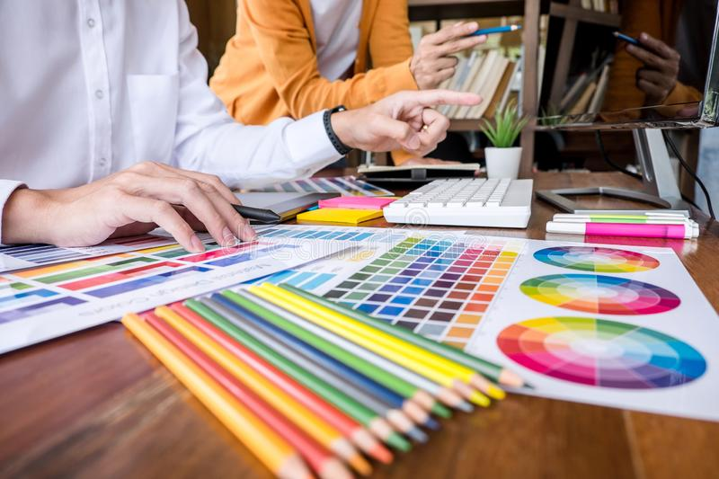 Two colleague creative graphic designer working on color selection and color swatches, drawing on graphics tablet at workplace stock image