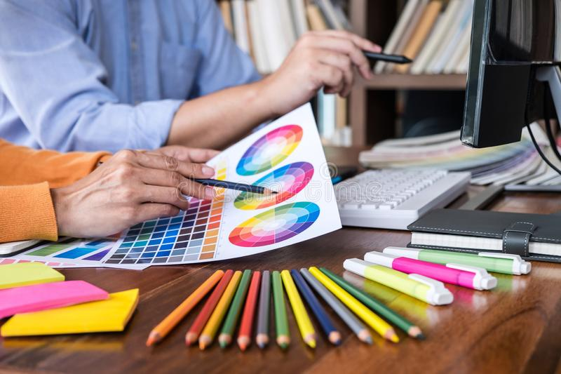 Two colleague creative graphic designer working on color selection and color swatches, drawing on graphics tablet at workplace royalty free stock photo