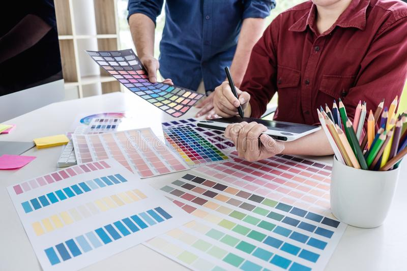Two colleague creative graphic designer working on color selection and color swatches, drawing on graphics tablet at workplace stock photo