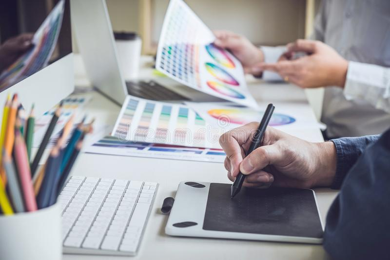 Two colleague creative graphic designer working on color selection and color swatches, drawing on graphics tablet at workplace royalty free stock photography