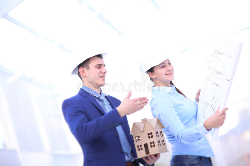 Two colleagues discussing data working and tablet, laptop with on on architectural project at construction site at desk stock image