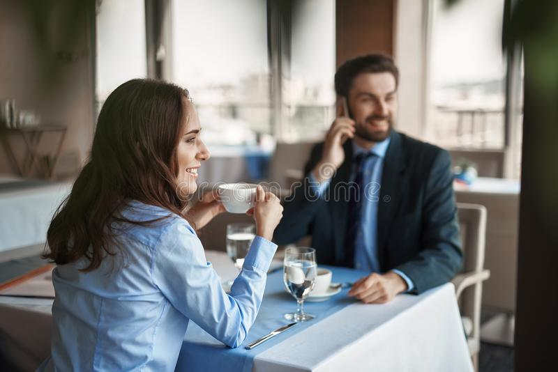 Two colleagues are having business lunch indoor. Business lunch in friendly atmosphere. Selective focus on smiling businesswoman drinking coffee while sitting in royalty free stock image