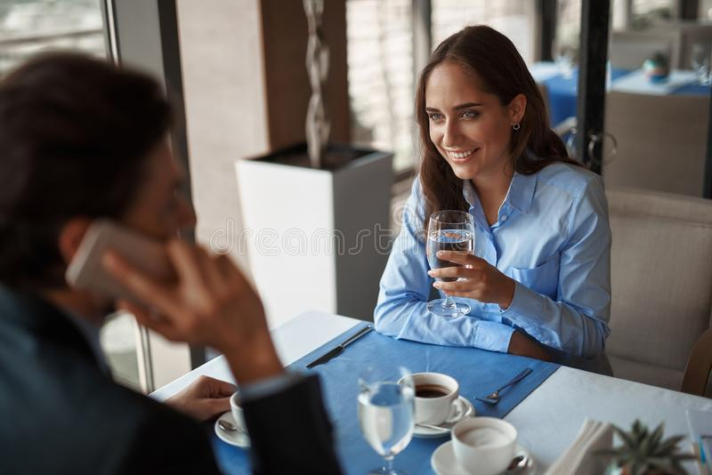 Two colleagues having business lunch in restaurant. Business lunch in friendly atmosphere. Portrait of smiling businesswoman drinking glass of water while royalty free stock images