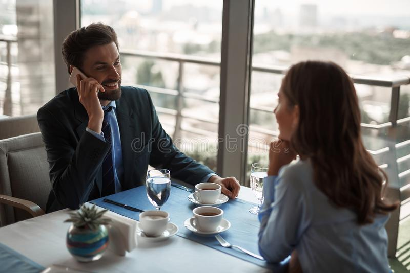 Two colleagues having business lunch in restaurant. Business lunch in friendly atmosphere. Portrait of young businessman talking by phone while sitting with royalty free stock images