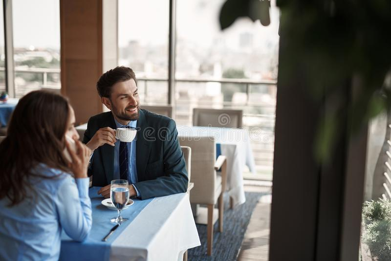 Two colleagues having business lunch in restaurant. Business lunch in friendly atmosphere. Selective focus on smiling businessman drinking coffee while sitting royalty free stock image