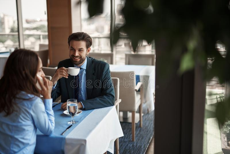 Two colleagues are having meeting in restaurant. Business lunch in friendly atmosphere. Selective focus on smiling businessman with cup of coffee looking at stock image