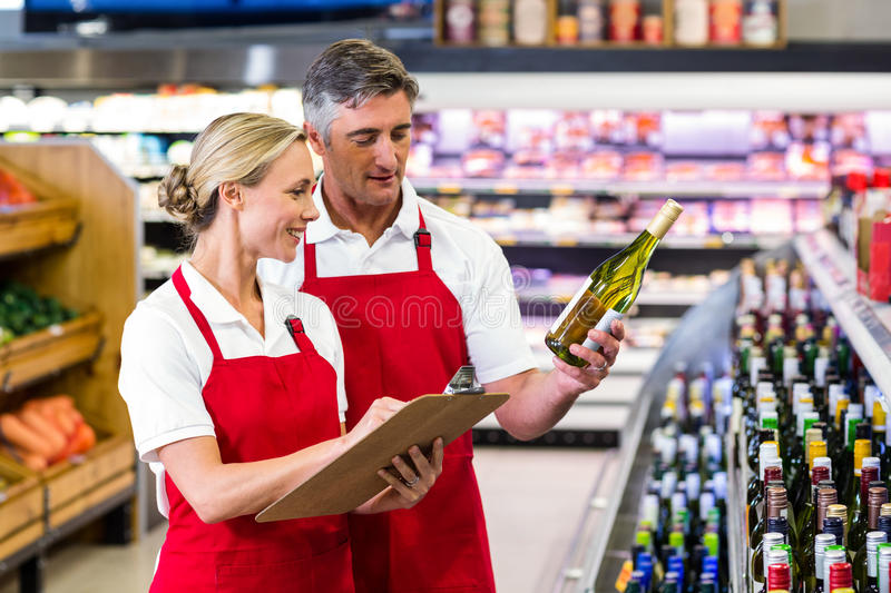 Two colleagues holding bottle of wine and writing on clipboard. At supermarket stock photos
