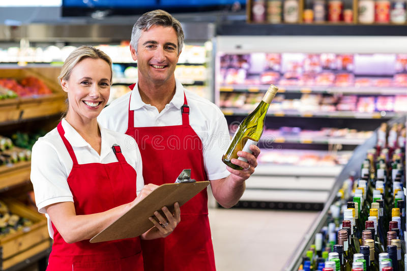 Two colleagues holding bottle of wine and writing on clipboard. At supermarket stock photography