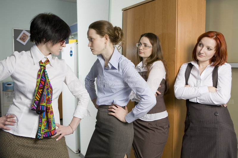 Two colleagues quarrel. Woman look at conflict. royalty free stock photo