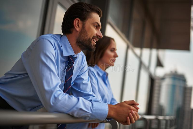 Two colleagues standing on balcony to have break. Concept of friendly communication between coworkers. Low angle portrait of young men and women standing on royalty free stock photos