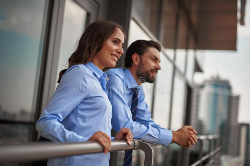 Two colleagues standing on balcony to have break. Concept of friendly communication between coworkers. Waist up portrait of young men and women in office clothes royalty free stock photo