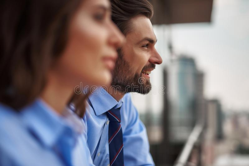 Two colleagues standing on balcony to have break. Friendly communication between coworkers. Close up portrait of young men and women in office clothes standing stock images