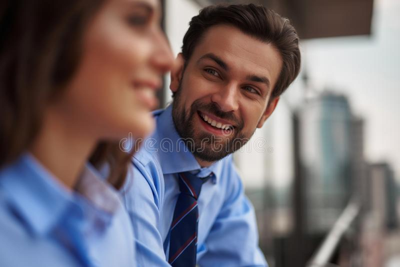 Two colleagues standing on balcony to have break. Friendly corporate culture. Close up selective focus on young men standing with women on office balcony while royalty free stock images