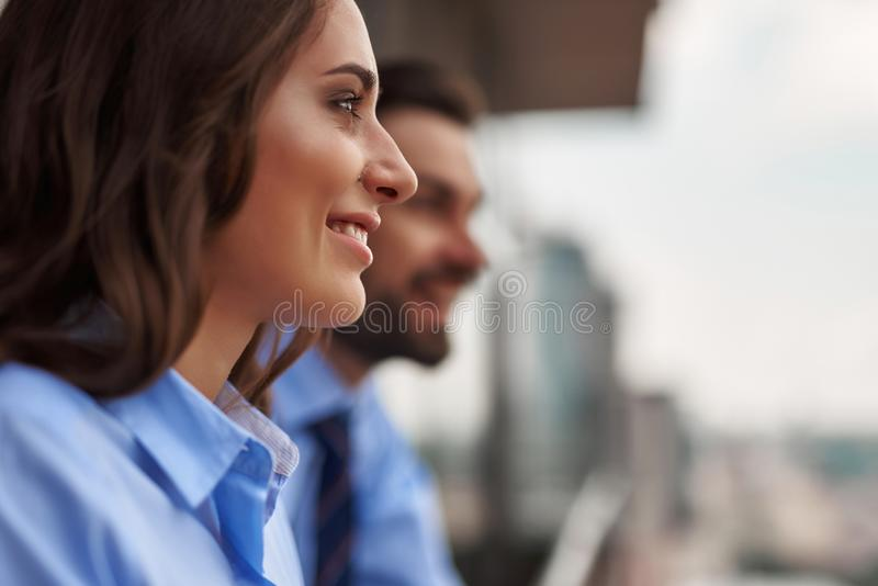 Two colleagues standing on balcony to have break. Friendly corporate culture. Close up selective focus on young women standing with men on office balcony while royalty free stock photos
