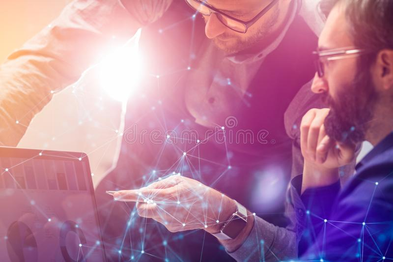 Two colleagues working on new global financial strategy analysis plan using laptop.Modern business team innovation royalty free stock image
