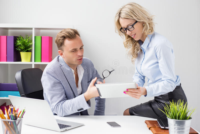 Two colleagues working together in office and looking at tablet computer royalty free stock photography