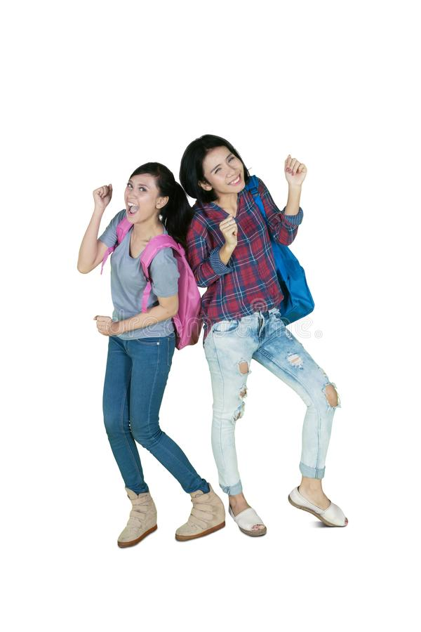 Two college students dancing in the studio. Full length of two female college students looks happy while dancing together in the studio stock photography