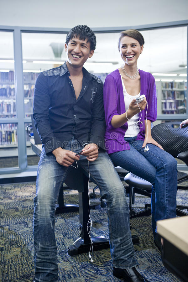 Two college students with music players in library stock photography