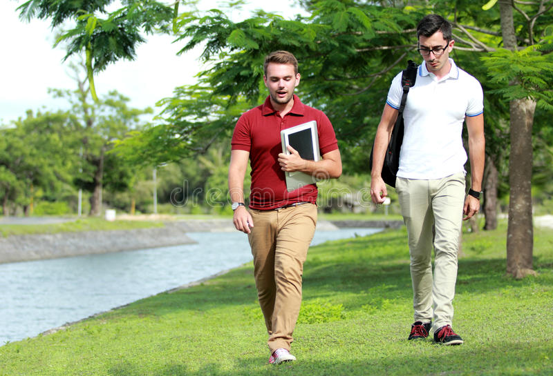 Two college students walking together at riverside royalty free stock photography