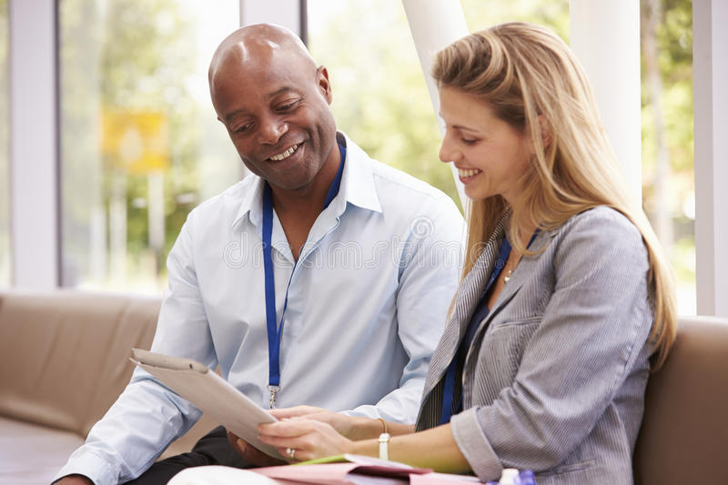 Two College Tutors Looking At Digital Tablet royalty free stock photography