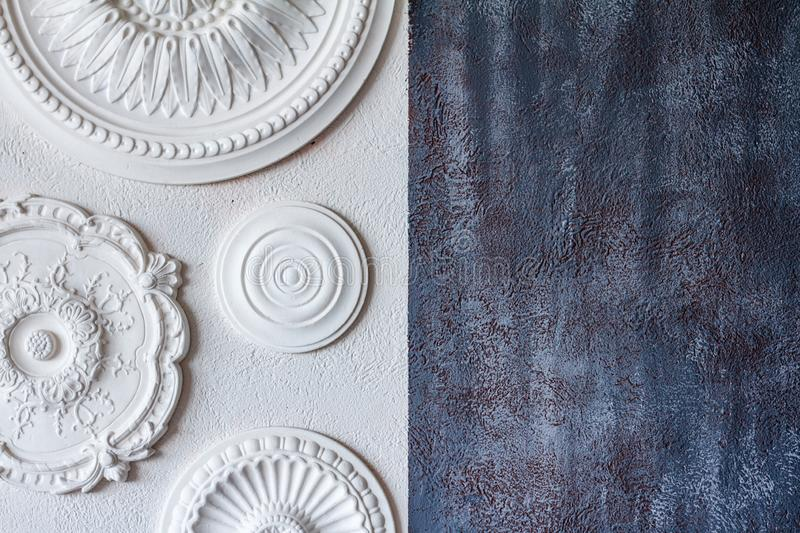 A two-color background, gray decorative plaster and a white wall with several white ceiling rosettes stock photography