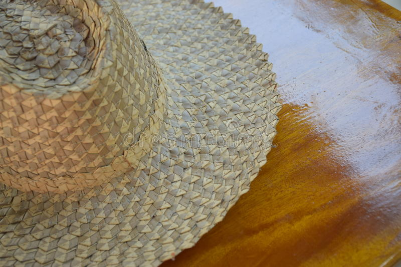 Two-color straw hat on wood table in calm and relaxing atmosphere. Two-colour neatly woven straw hat on wood table in calm and relaxing atmosphere royalty free stock photos