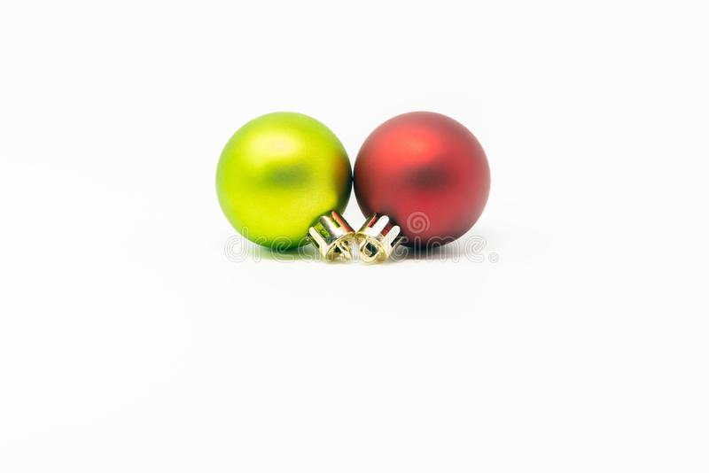Two colored Christmas balls on white background. Red and green matte spherical Christmas decorations isolated on white background. Conceptual image for royalty free stock photos