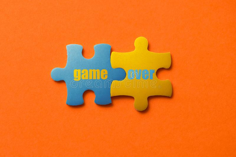 Two colored details of puzzle with text Game Over on orange background, Yellow and Blue, close up.  stock photo
