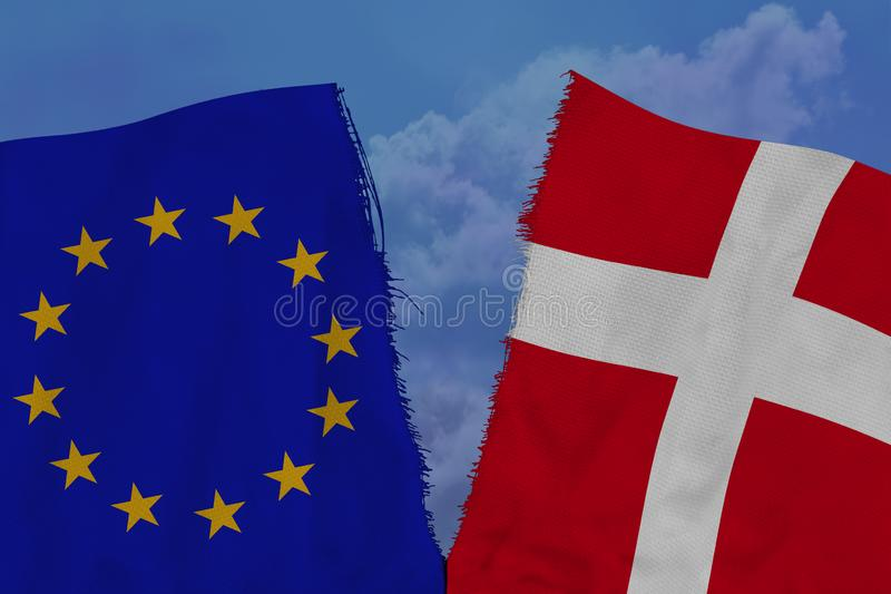 Two colored flags on torn fabric, a symbol of international relations between the European Union and Denmark, the concept of. Global business, the deterioration stock photography
