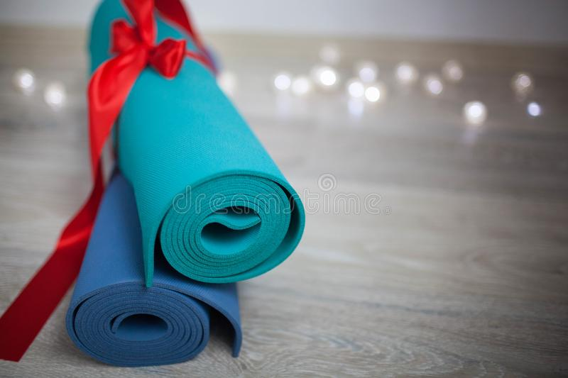 Two colored yoga Mat with a gift ribbon royalty free stock photos