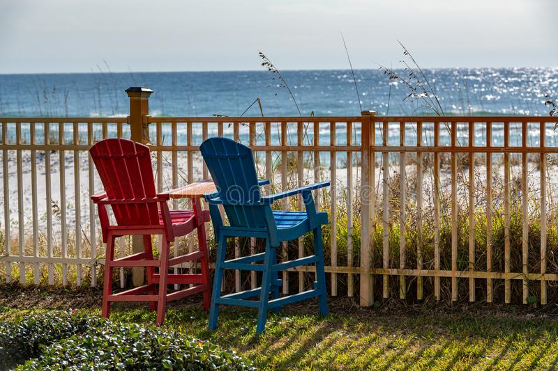 Two colorful Adirondack chairs await tourists wishing to enjoy the beautiful beach and gulf landscape and seascape. Pensacola Beach, Florida royalty free stock photography