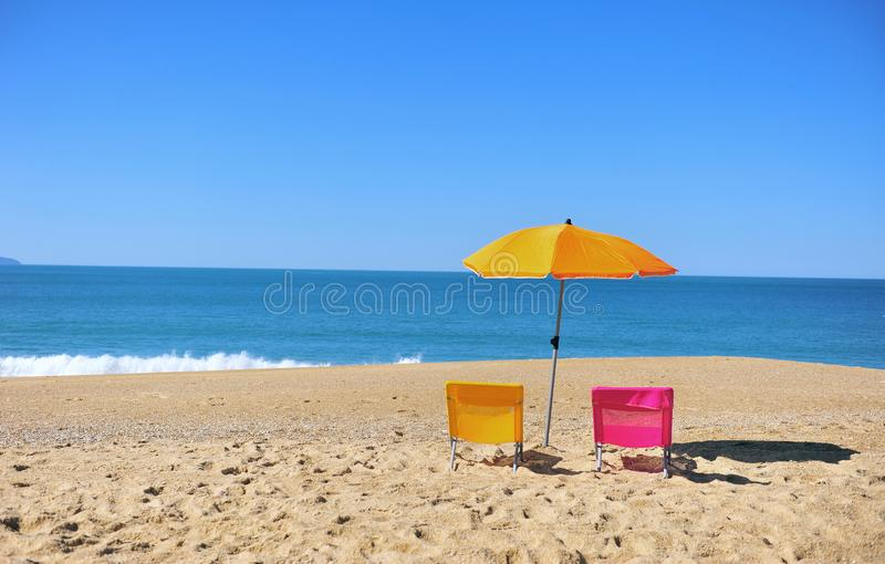Two colorful beach chairs and umbrella with blue sea water stock images