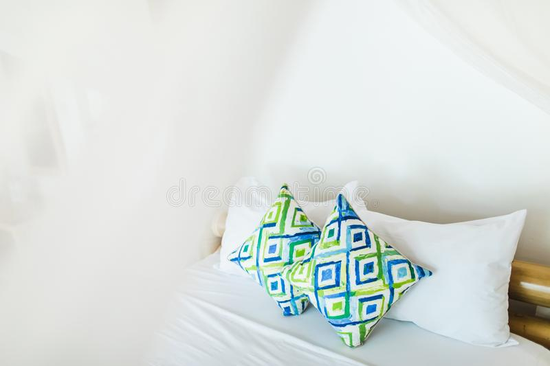 Two colorful blue and green pillows on white bed. Two colorful blue and green ornamental pillows on white bed. Light cozy interior design. Empty place stock photos