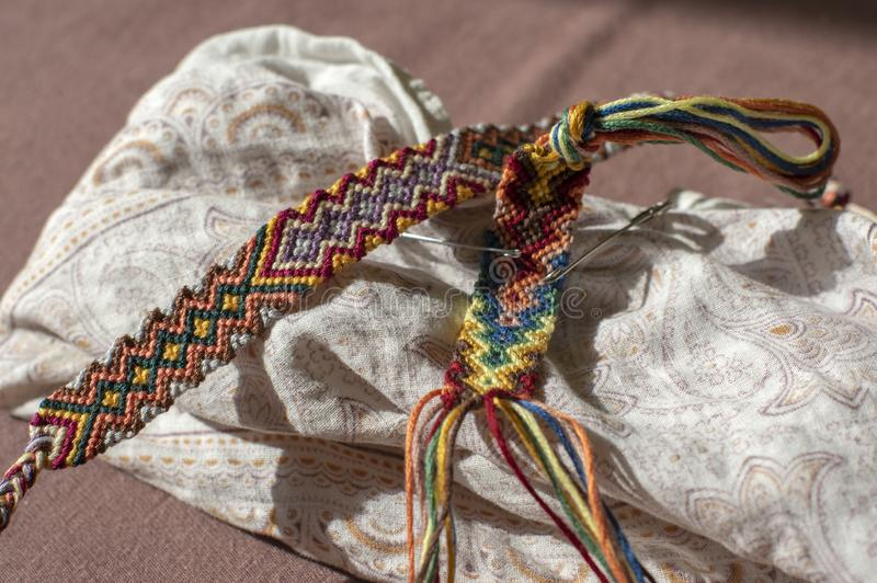 Two colorful handmade homemade natural woven bracelets of friendship in process royalty free stock photos