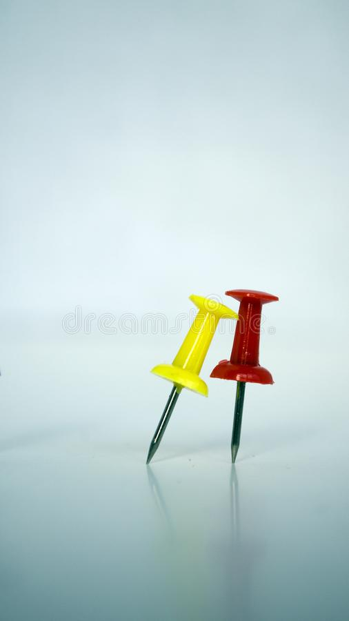 Two colorful pushpins on white blue background stock image