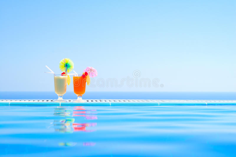 Two Colorful Tropical Cocktails near the Swimming Pool on Background of Warm Blue Sea. Exotic Summer Vacation. stock photo
