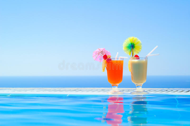 Two Colorful Tropical Cocktails near the Swimming Pool on Background of Warm Blue Sea. Exotic Summer Vacation. stock photography