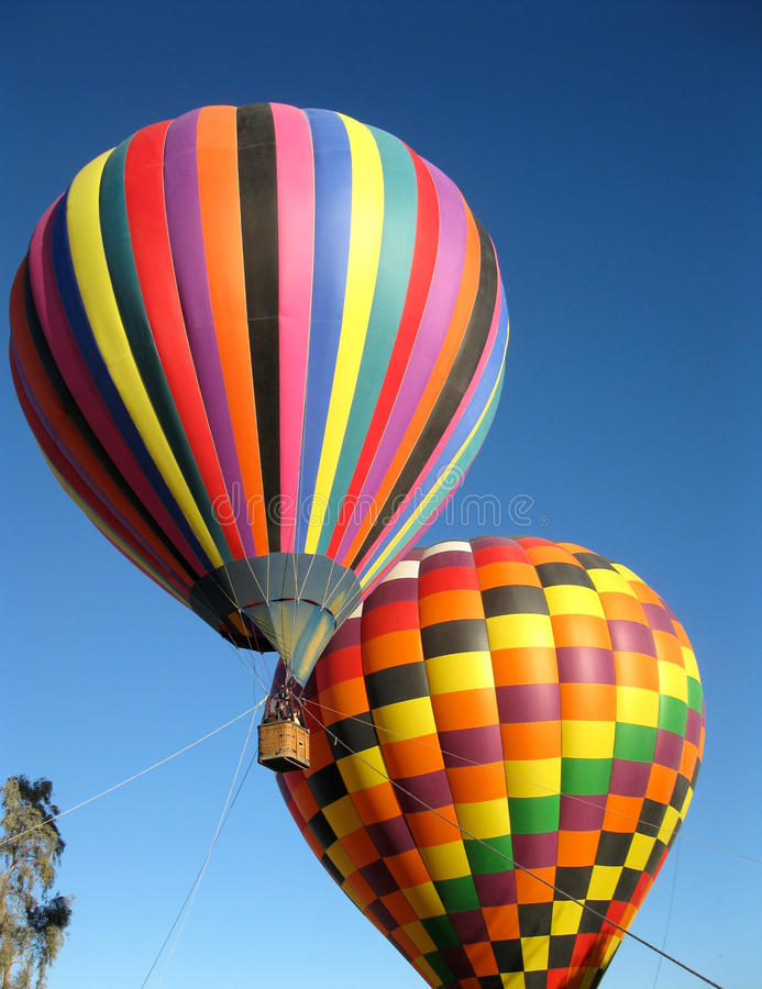 Two colourful hot air balloons in a Blue Sky. Two colourful hot air balloons drifting in a Blue Sky stock image
