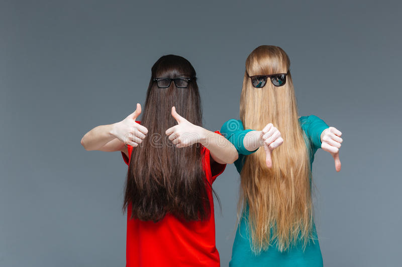 Two comical women with faces covered by long hair gesturing stock photos