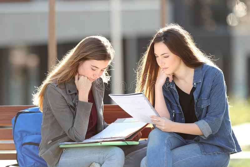 Concentrated students studying in a park. Two concentrated students studying sitting on a bench in a park stock images