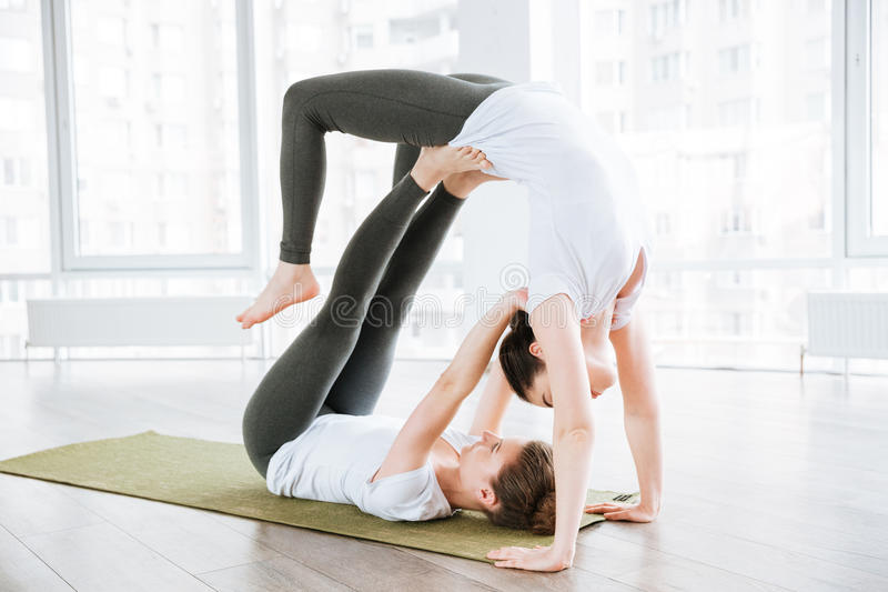 Two concentrated young women doing acrobatic yoga position stock images