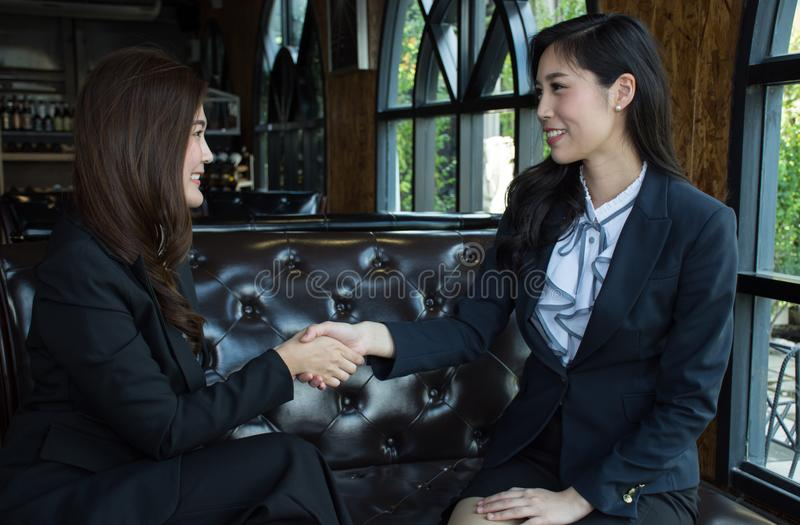 Two confident Asian business woman shaking hands during a meeting in the office royalty free stock photos
