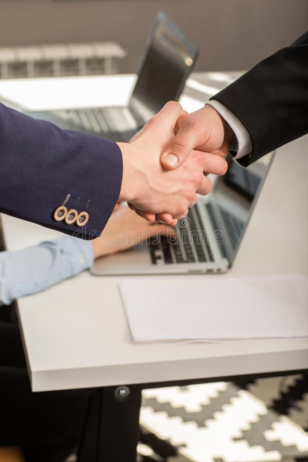 Two confident business man shaking hands during a meeting in the office stock images