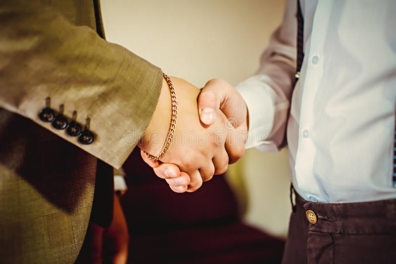 Two confident business man shaking hands during a meeting in the office, success, dealing, greeting and partner concept stock photo