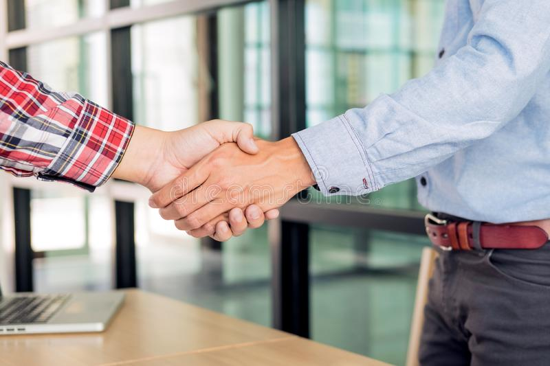 Two confident business man shaking hands during a meeting in the office, success, dealing, greeting and partner concept royalty free stock photography