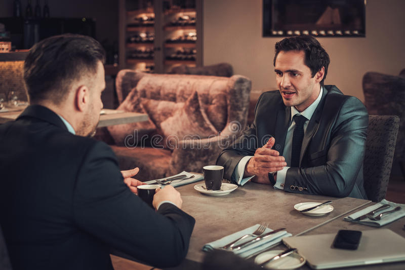 Two confident business men have business lunch at restaurant royalty free stock photography