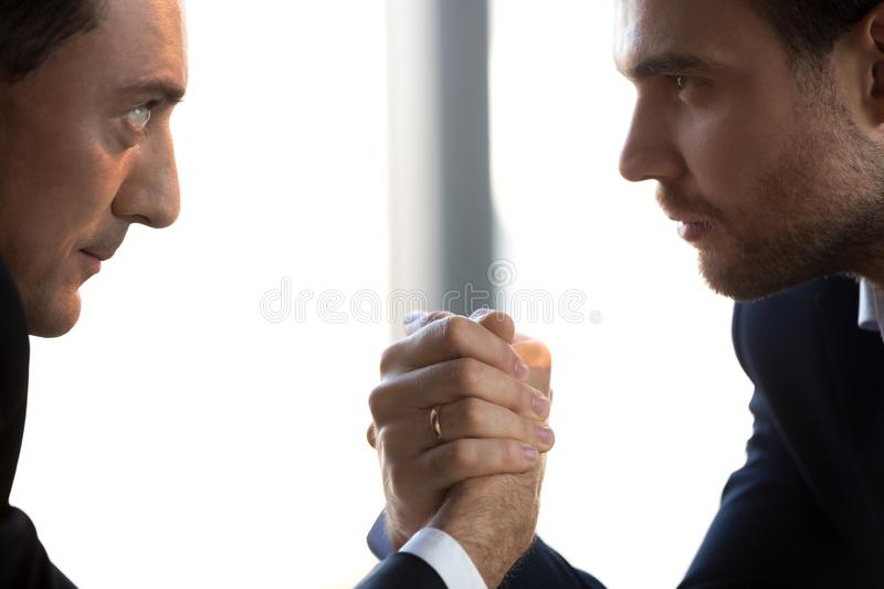 Two confident businessmen compete arm wrestling looking in eyes, closeup. Two confident businessmen compete arm wrestling looking in eyes showing power royalty free stock images