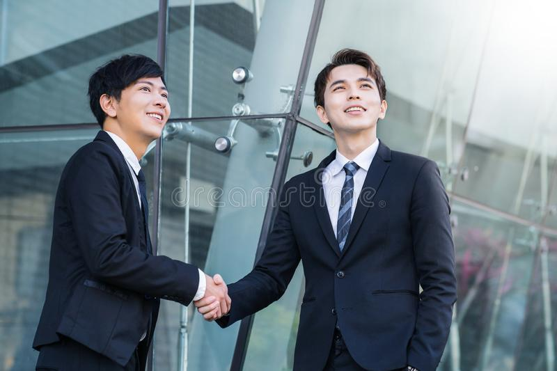 confident businessmen shaking hands and smiling royalty free stock photography