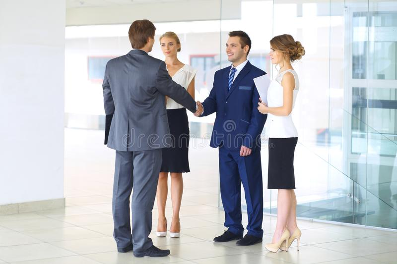 Two confident businessmen shaking hands and smiling while standing at office together with group of colleagues stock photo
