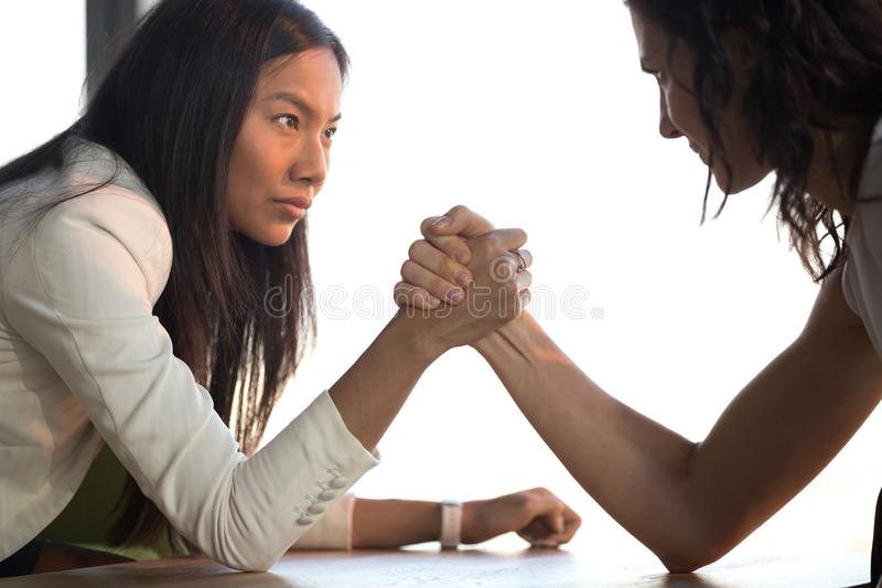 Young asian and caucasian businesswomen armwrestling struggle for leadership. Two confident diverse businesswomen compete arm wrestling look in eyes feel jealous royalty free stock images